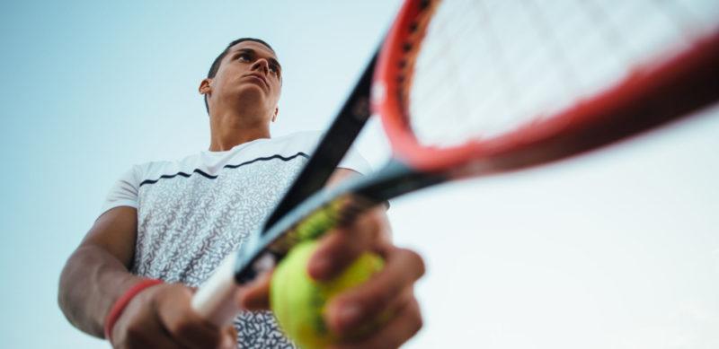 Young man playing tennis preparing to serve