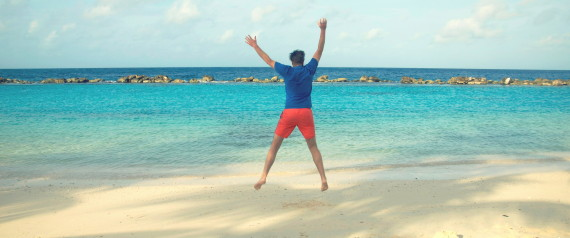 Happy man jumping in the air on the beach