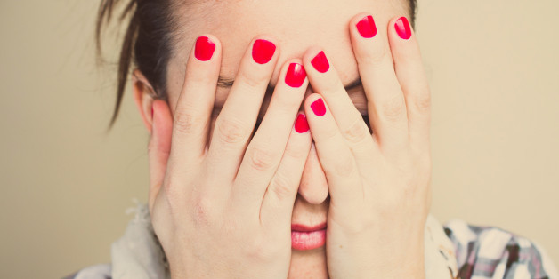 Worried. Girl with hands on face and red nails