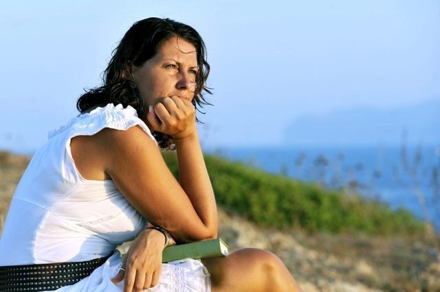 attractive 40s mature woman reading and looking at horizon pensive