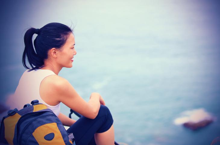 young asian woman hiker sit mountain rock